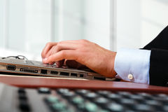 Worker typing on a laptop computer Royalty Free Stock Photos