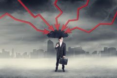 Worker with umbrella and declining arrows Stock Photography