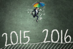 Worker with umbrella jumps above numbers 2015 to 2016 Royalty Free Stock Photo
