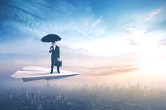 Worker with umbrella on paper aircraft Stock Photos