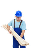 Worker in uniform carrying wooden planks Stock Photo
