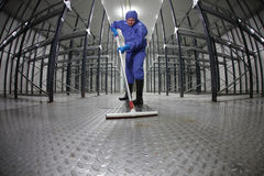 Worker uniform cleaning floor in storehouse