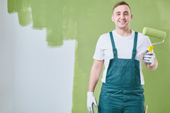 Worker in uniform. Happy construction worker in uniform ready to paint the wall stock images