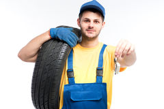 Worker in uniform holds tire and car keys in hands Royalty Free Stock Photo