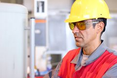 Worker In Uniform - Protective Workwear. Portrait of a worker wearing protective helmet and safety glasses Royalty Free Stock Photos