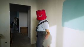 Worker in uniform with red bucket on his head have fun and dancing stock video