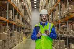 Worker in uniform using mobile phone at warehouse. Warehouse worker in hard hat using mobile phone royalty free stock photos