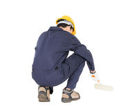 Worker in a uniform using a paint roller is painting invisible f Royalty Free Stock Images