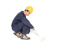 Worker in a uniform using a paint roller is painting invisible f. Young worker in a uniform using a paint roller is painting invisible floor, isolated on white Stock Photo
