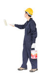 Worker in uniform using paint roller is painting invisible wall. Young worker in uniform hold color can and using paint roller is painting invisible wall Royalty Free Stock Photos