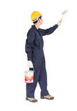 Worker in uniform using paint roller is painting invisible wall. Young worker in uniform hold color can and using paint roller is painting invisible wall Stock Images