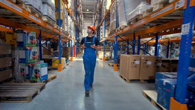 A worker in a uniform walks along a warehouse corridor. stock video footage