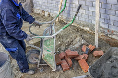 Worker unload a wheelbarrow with bricks 2. Worker unload a wheelbarrow with bricks, at a building site. collects bricks for the bricklayer Royalty Free Stock Photography