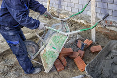 Worker unload a wheelbarrow with bricks. At a building site. collects bricks for the bricklayer Royalty Free Stock Photography