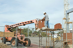 Worker Unloading Brick Stock Image