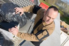 Worker unloading rubbish bags at tip. Worker unloading rubbish bags at the tip Royalty Free Stock Image