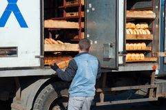 The worker unloads fresh bread from the truck stock photography