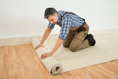Worker unrolling carpet on floor Stock Photography