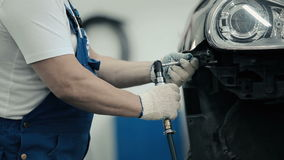 The worker unscrews the screws from the bumper. Close-up. The man unscrews the three screws screwdriver. A man wearing a blue work overalls and gloves. Man stock footage