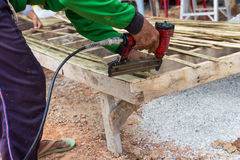 The worker use the drill to assemble the wooden seat Stock Photos