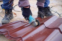 Worker use grinding machine for cutting metal roof sheets. A roofer uses an electric tool when building a house.  Stock Photo
