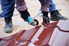 Worker use grinding machine for cutting metal roof sheets. A roofer uses an electric tool when building a house.  Stock Image