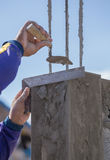 Worker use iron ruler snd trowel plastering the poles Royalty Free Stock Image