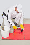 Worker use Rubber Hummer for Tiles ajusment Royalty Free Stock Photography