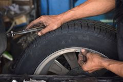 Worker use small lead for wheel Balancing. royalty free stock photo