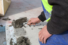 Worker use spatula for plastering a floor. royalty free stock photos