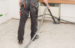 Worker use vacuum cleaner in construction. Worker man use vacuum cleaner in construction Royalty Free Stock Photo