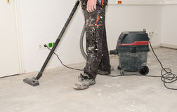 Worker use vacuum cleaner in construction. Worker man use vacuum cleaner in construction Royalty Free Stock Images