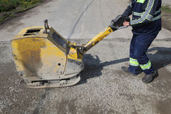 Worker use vibratory plate compactor at road construction site stock photography