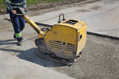 Worker use vibratory plate compactor at road construction site. Worker use vibratory plate compactor compacting gravel at road construction site Stock Image