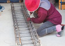 Worker used pliers wire tie tightening of steel bar reinforcement Stock Photo
