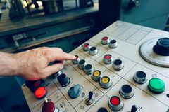 The worker uses the control panel of the CNC machine to process the material. stock photos