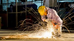 Worker uses grinding cut metal, focus on flash light line of sha. The worker uses grinding cut metal, focus on flash light line of sharp spark,in low light Royalty Free Stock Image