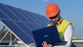 Worker uses his laptop, while examining the solar panels on the roof. 4K. Worker uses his laptop, while examining the solar panels on the roof stock video