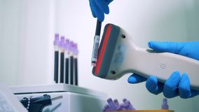 Worker uses scanner to check information on tubes of blood samples at a hospital. HD. Worker uses scanner to check information on tubes of blood samples at a stock video