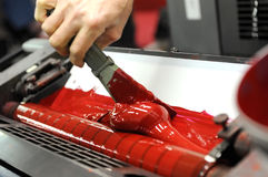 Worker uses specialized spatula to apply red paint. To industrial printer Royalty Free Stock Photography