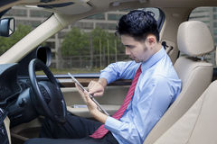Worker uses tablet while driving a car Royalty Free Stock Photo
