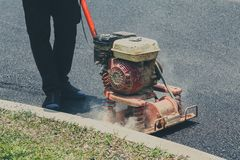 Worker uses vibratory plate compactor compacting asphalt royalty free stock photo