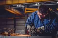 Worker Using Angle Grinder. In Factory and throwing sparks Royalty Free Stock Photography