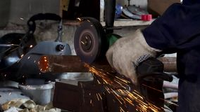 Worker using angle grinder in factory and throwing sparks. Frame. Man wearing protective uniform and cutting metal with. Worker using angle grinder in factory stock video footage