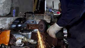 Worker using angle grinder in factory and throwing sparks. Frame. Man wearing protective uniform and cutting metal with. Worker using angle grinder in factory stock video