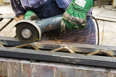 Worker using angle grinder. On a steel structure Royalty Free Stock Photography