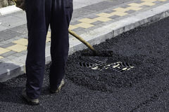 Worker using asphalt lute to level the asphalt 2 Royalty Free Stock Image
