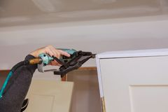 Worker using brad nail gun installs doors. Carpenter using a nail gun Air gun for nailing using nail gun Royalty Free Stock Images