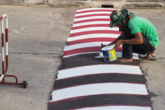 Worker using brush for painting white line on the road. CHIANGMAI - SEPTEMBER 11: The worker use brush for painting white line on the road for caution to reduce Royalty Free Stock Image