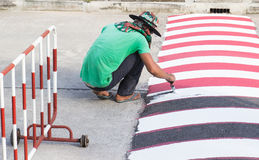 Worker using brush for painting white line on the road. The worker use brush for painting white line on the road for caution to reduce the car speed in Stock Images